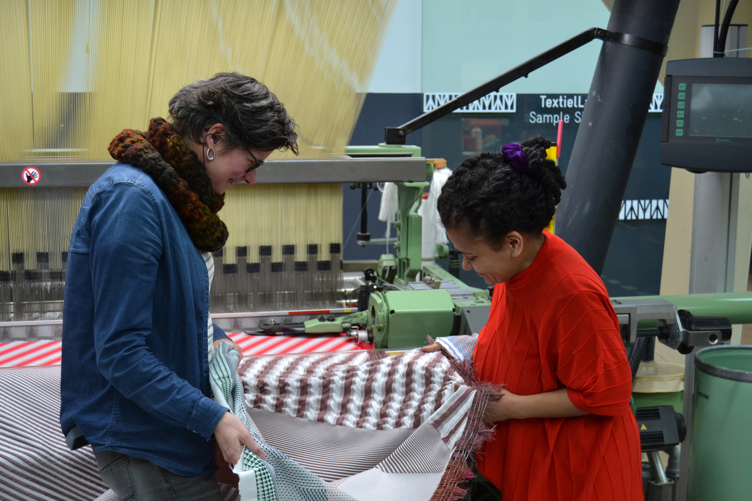 Marjan Van Oeffelt, product developer at the TextielLab and Ta'Yali Wetzel - both smiling - stand facing each other holding and examining a woven fabric that just came off the weaving machine they are stading in front of. The Jacquard harness and part of the weft rapier are visible in the background.